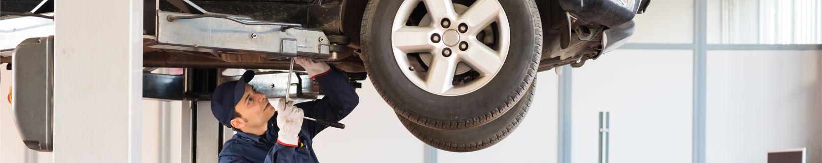 Car Mechanic Working Underneath a Car